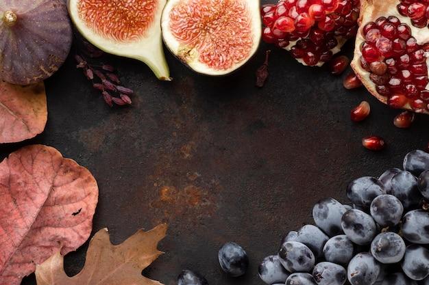 Frutas de outono de romã e uvas copiam espaço