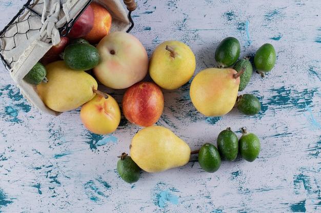 Frutas de outono misturadas em uma cesta metálica