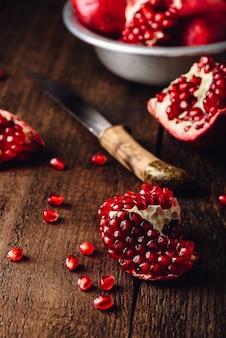 Frutas de romã com faca em superfície de madeira rústica