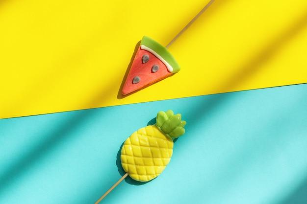 Frutas de verão abacaxi e pirulitos de melancia no fundo amarelo azul com luz e sombra dura