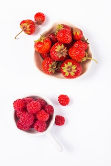Frutas de verão conceito morango e rasberry em copo cerâmico no fundo branco
