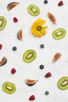 Frutas de verão figos kiwi framboesas mirtilos e pétalas de flores em fundo branco de madeira