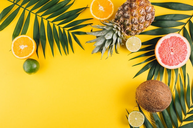 Frutas de verão. folhas de palmeira, abacaxi, coco, toranja, laranja e cal tropicais no fundo amarelo.