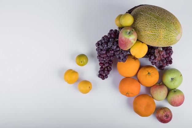 Frutas de verão se misturam em uma vista superior branca.