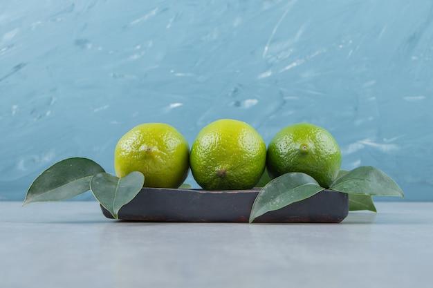 Frutas deliciosas de limão com folhas na placa preta.