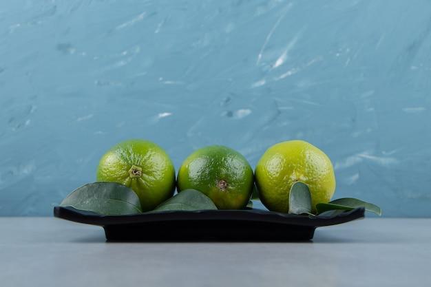 Frutas deliciosas de limão na placa preta.