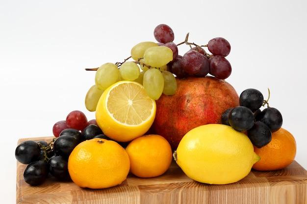 Frutas diferentes em uma placa de madeira isolada