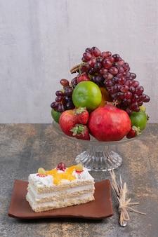 Frutas doces diferentes em prato de vidro com um pedaço de bolo em prato escuro