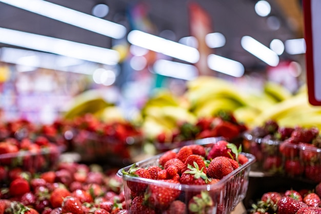 Frutas e bagas coloridas em bananas e morangos de loja de mercado de fazendeiros vendidos em supermercado super bazar ...