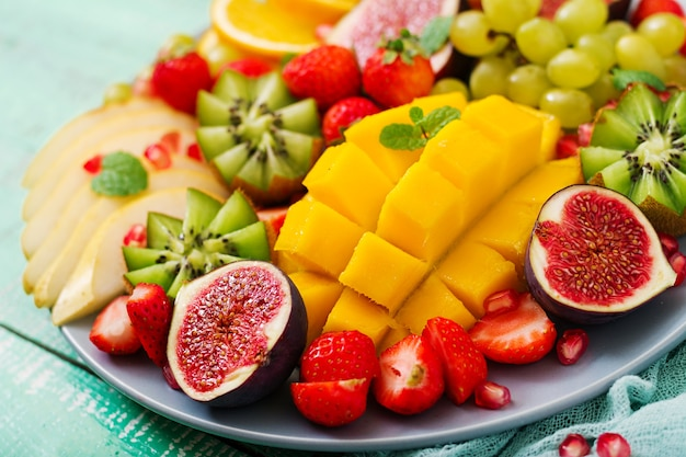 Frutas e bagas de bandeja. manga, kiwi, figo, morango, uvas, pêra e laranja.