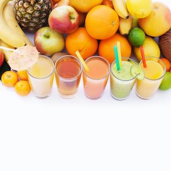 Frutas e bebidas, vista superior de macro de smoothies de verão isolada no branco.