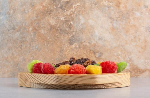 Frutas e cerejas secas coloridas na superfície do concreto.