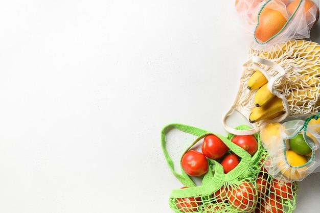 Frutas e cítricos em bolsas reutilizáveis de malha ecológica em fundo rosa. compras com desperdício zero.