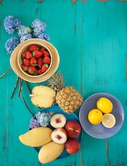 Frutas e flores na mesa azul