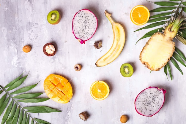 Frutas e folhas de palmeira no fundo branco. frutas tropicais.