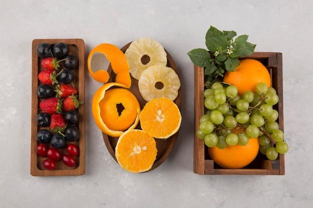 Frutas e frutas silvestres em travessas de madeira no centro