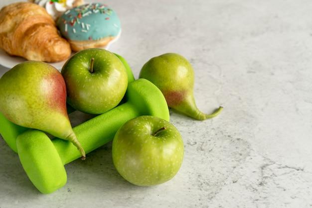 Frutas e halteres verde no concreto texturizado