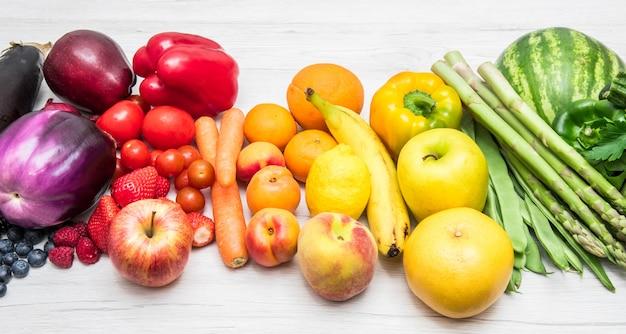 Frutas e legumes arco-íris na madeira