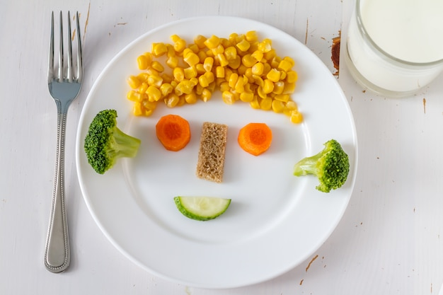 Frutas e legumes arranjados para parecerem atraentes para as crianças no rosto engraçado