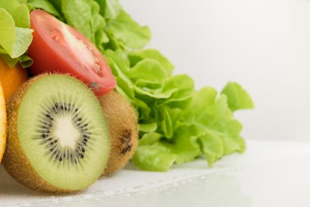 Frutas e legumes de quivi no branco. tomate e alface. alimentos saudáveis.