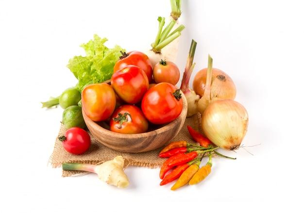 Frutas e legumes em uma tigela de madeira no fundo branco