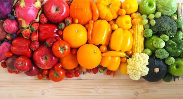 Frutas e legumes frescas coloridas no fundo de madeira.