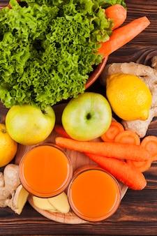 Frutas e legumes frescos com suco na mesa