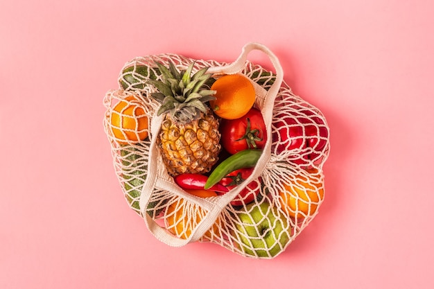 Frutas e legumes frescos em malha de saco, vista superior.