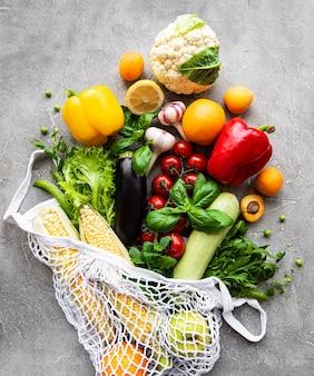 Frutas e legumes frescos em um saco de barbante ecológico em uma superfície de concreto