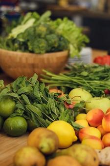 Frutas e legumes frescos em uma mesa de madeira.