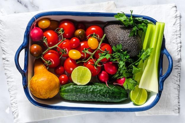 Frutas e legumes frescos multicoloridos brilhantes do verão em uma mesa em uma assadeira. cozinhar, ingredientes para salada