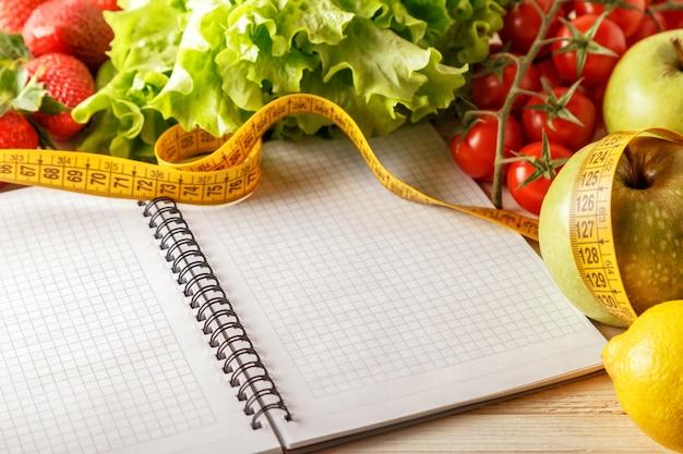 Frutas e legumes orgânicos frescos, abra o caderno em branco e caneta na mesa de madeira.