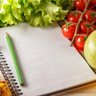 Frutas e legumes orgânicos frescos, caneta e caderno em branco aberto