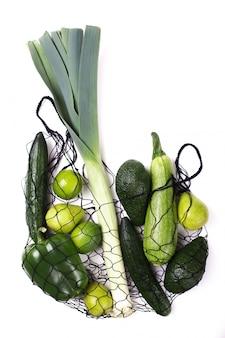 Frutas e legumes verdes em saco ecológico líquido