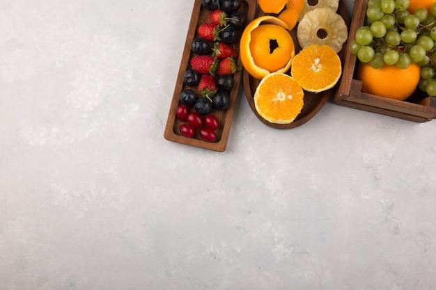 Frutas e morangos em bandejas de madeira no canto superior