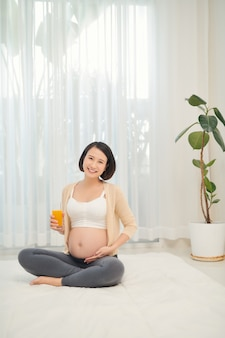 Frutas e suco de laranja nas mãos de uma mulher grávida.
