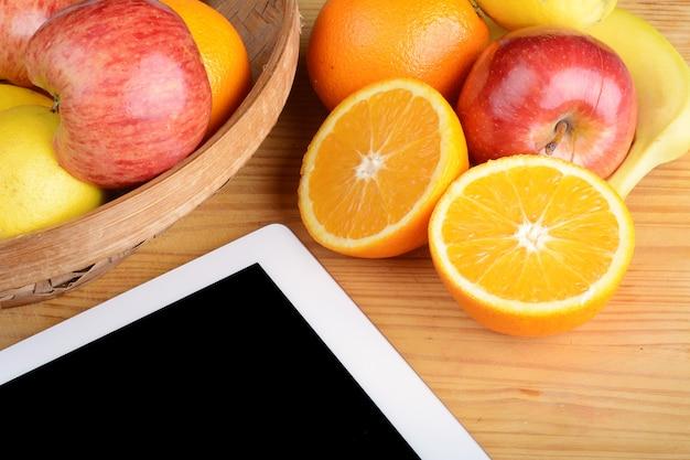 Frutas e um tablet pc na mesa de madeira.