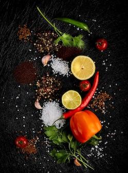 Frutas e vegetais com especiarias em fundo de madeira escura