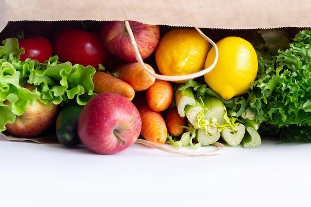 Frutas e vegetais crus frescos em um saco de papel ecológico isolado em uma parede branca