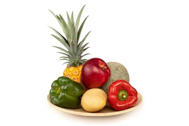 Frutas e vegetais em bandejas de madeira, isoladas no fundo branco.