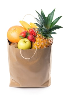 Frutas e vegetais em sacola de papel isolada sobre o branco