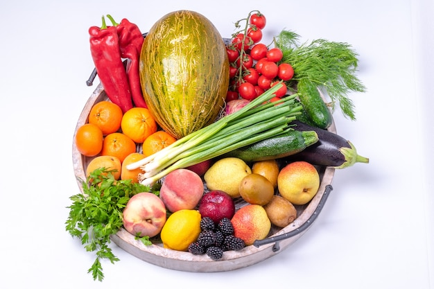 Frutas e vegetais em uma bandeja de madeira isolada no fundo branco