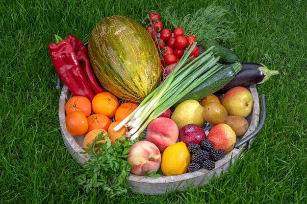 Frutas e vegetais em uma bandeja de madeira na grama verde, foto da colheita.