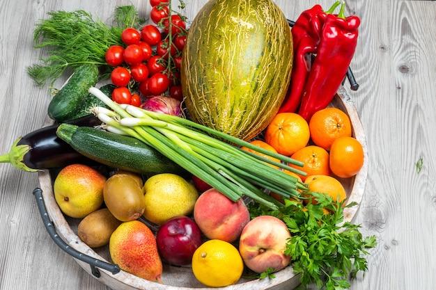 Frutas e vegetais em uma bandeja de madeira no fundo cinza da mesa de madeira