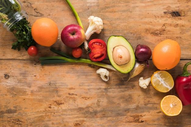 Frutas e vegetais frescos dispostos em uma fileira na mesa de madeira