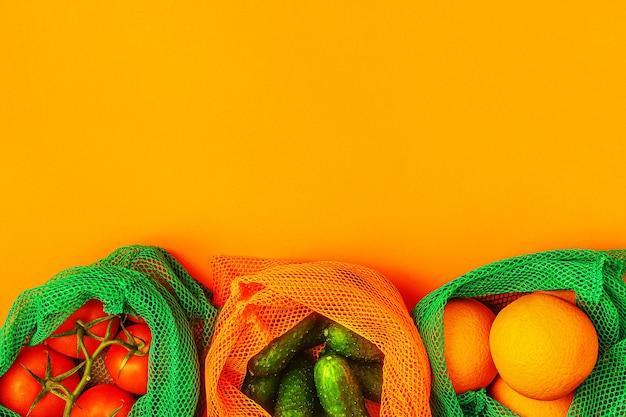 Frutas e vegetais frescos em sacos de malha têxteis reutilizáveis, compras ecológicas, conceito de desperdício zero.
