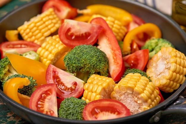 Frutas e vegetais frescos em uma frigideira em um fundo de madeira velha