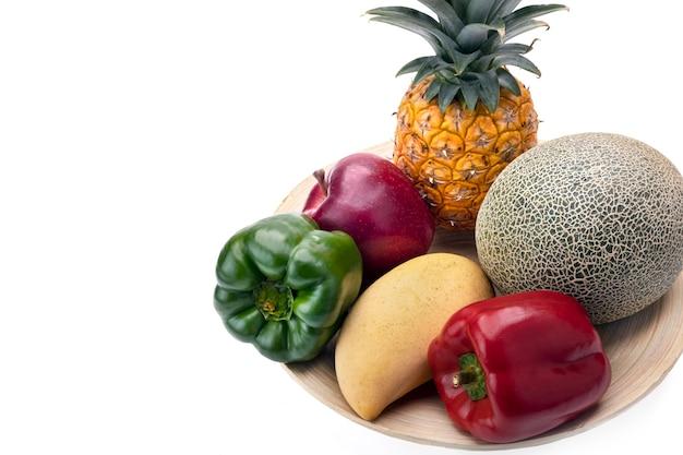 Frutas e vegetais frescos em uma placa de madeira, isolados no fundo branco.