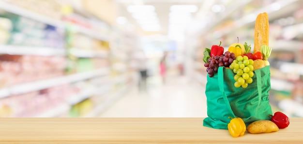 Frutas e vegetais frescos em uma sacola de compras verde reutilizável na mesa de madeira com o fundo desfocado borrado da mercearia do supermercado