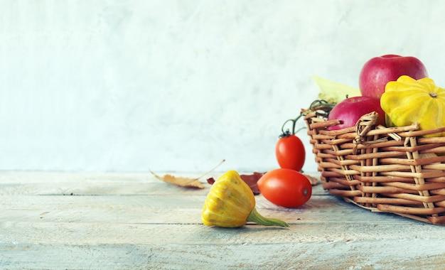 Frutas e vegetais frescos maduros em uma cesta em um conceito de colheita de mesa de madeira dia de ação de graças